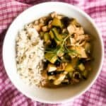 A bowl of Quick Rosemary Lemon Chicken Stew with rice on a pink and white checkered kitchen towel