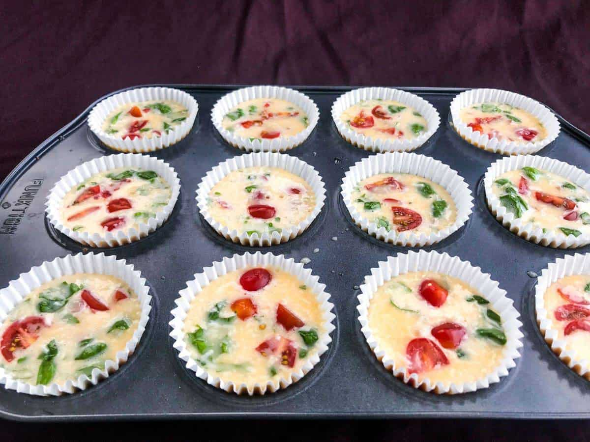 Healthy italian breakfast egg muffins on a mufifn tray before baking on a purple surface
