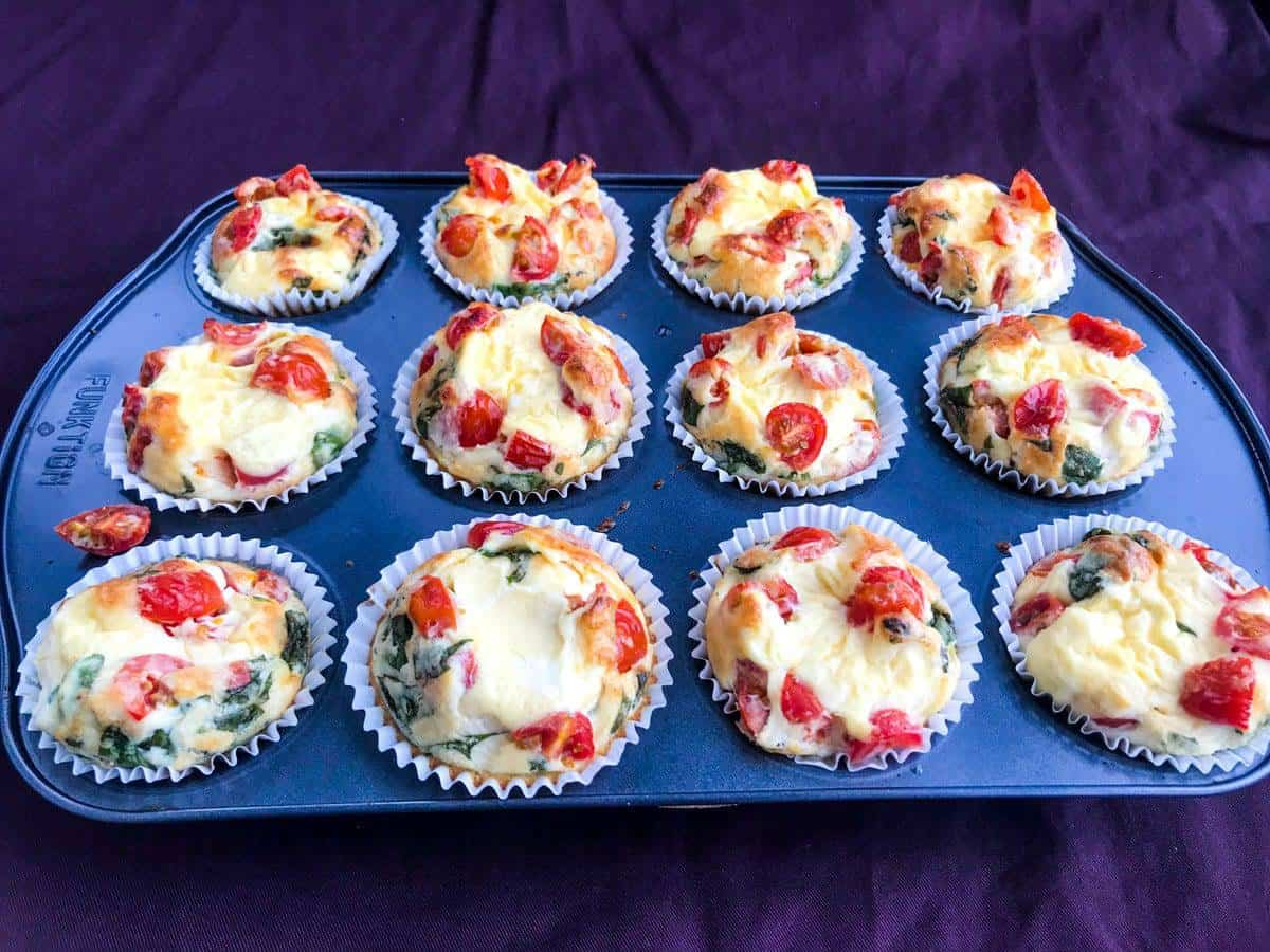 Healthy italian breakfast egg muffins on a muffin tray on a purple surface