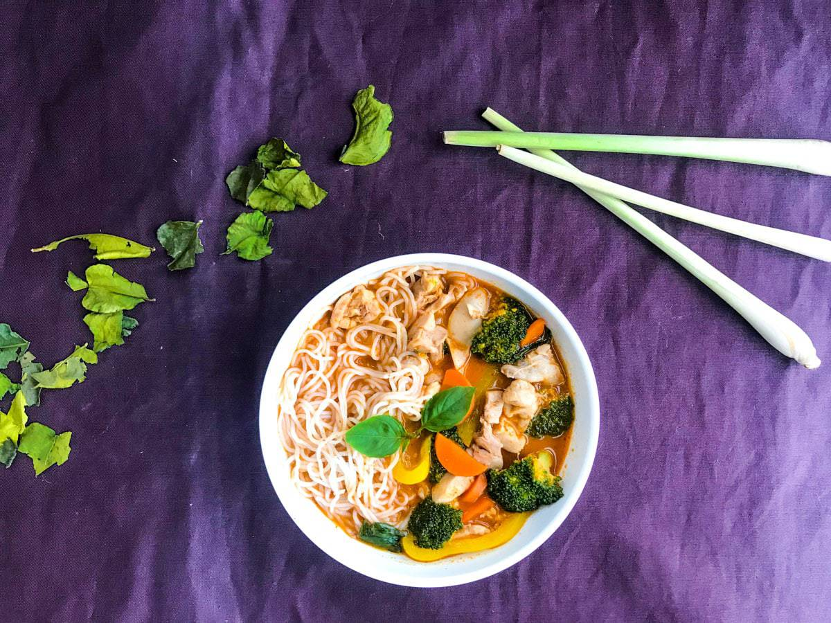 thai chicken noodle soup in a white bowl on a purple surface with lemon grass and kaffir lime leaves