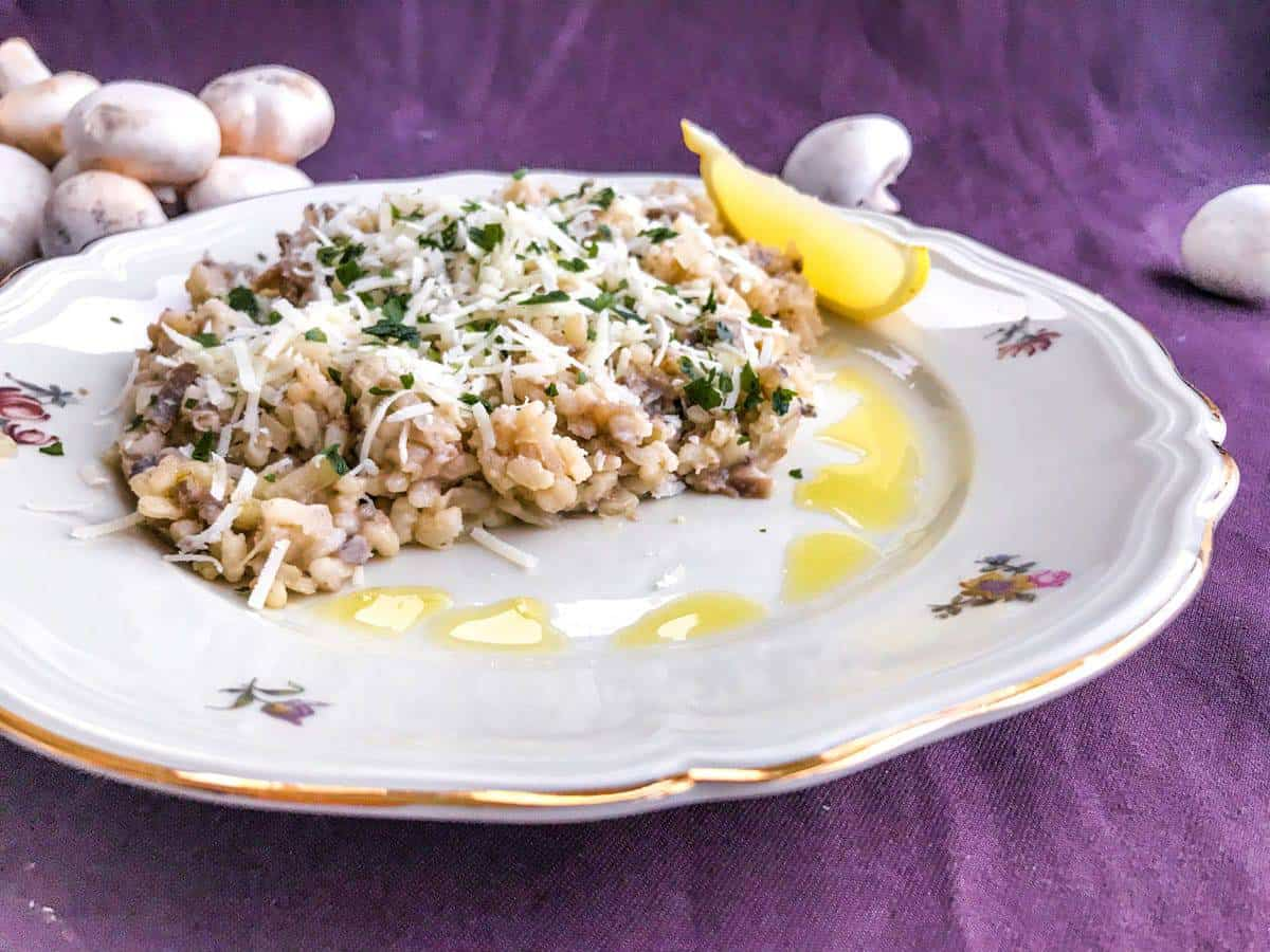 Creamy truffled mushroom risotto with a lemon wedge on a plate on a purple surface